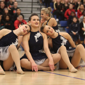Abby Markowski (12), Madeline Andrews (11) and Paige Lambert (9) get ready to start their performance. Because LC hosted the competition, they were unable to compete with the other teams.