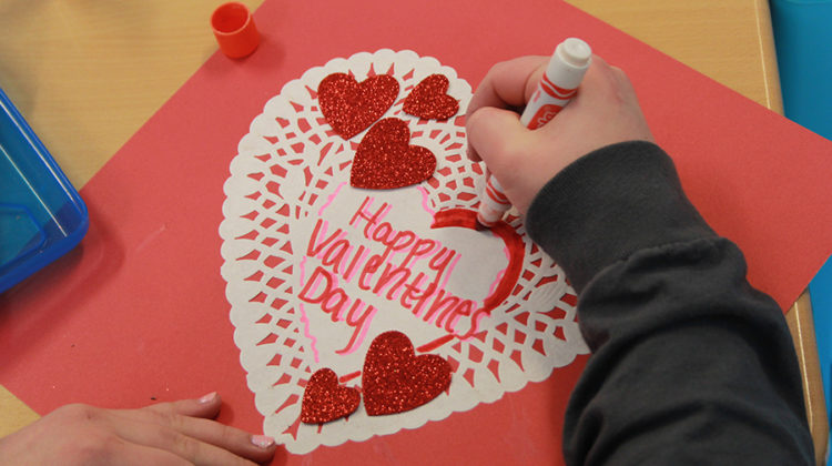 Kaitlyn Kennedy (10) works on decorating the card for Valentine's Day. Kennedy decorated the cards with her friends in the club.