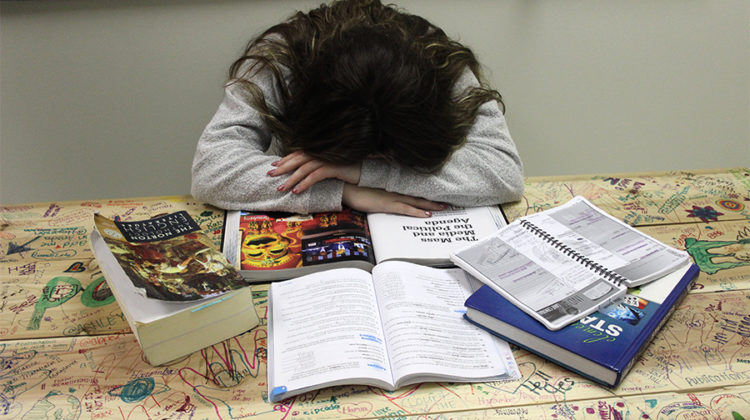 A student lays their head on their book showing they have no motivation. Senioritis has been hitting seniors harder towards the end of the school year.