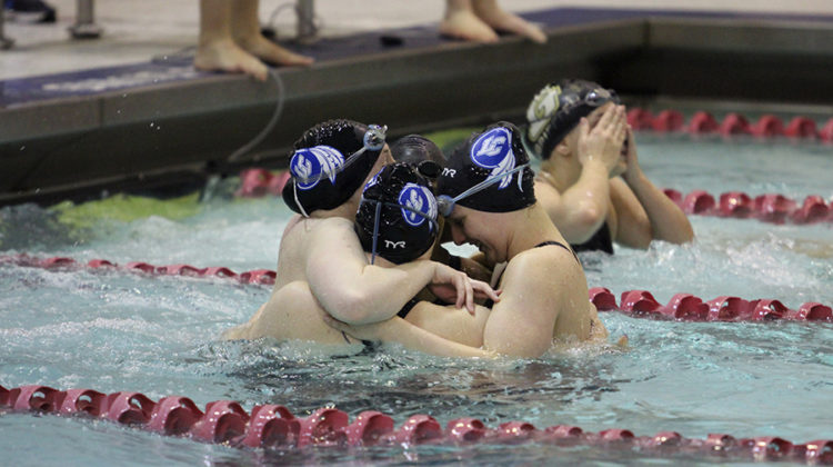 Savanna Spears (11), Maggie DePirro (9), Rachel Albright (11) and Sara Erwin (12) hug after earning third in the 200-yard freestyle relay. This relay event helped the team accumulate points.