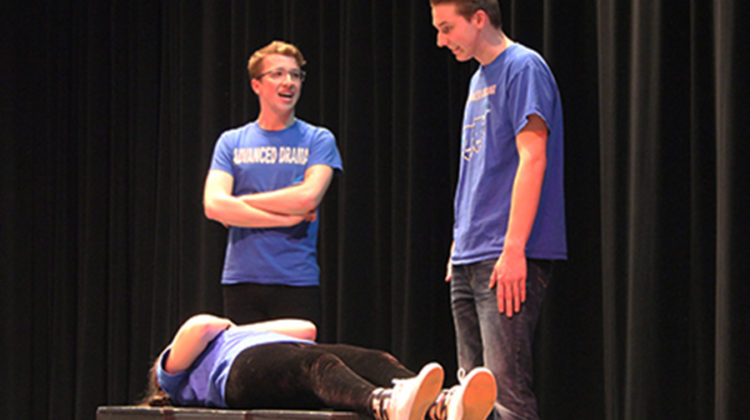 Adam Gustas (12) and William Kruzan (12) stand over the body of their local mailman, Hannah Souronis (12). At the end of the skit Souronis hopped out of her casket and walked right out the door.