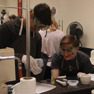 Patel and Alexander Glass (10) share a laugh as they prep for the experiment. The students did the first half this day and the experiment will roll over into next class.