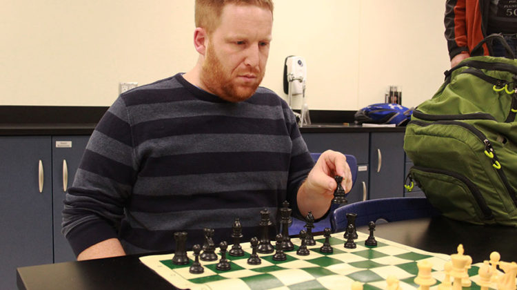Dr. Dustin Verpooten, Science, moves his black knight into position. Verpooten has been the sponsor of the Chess Club for five years.