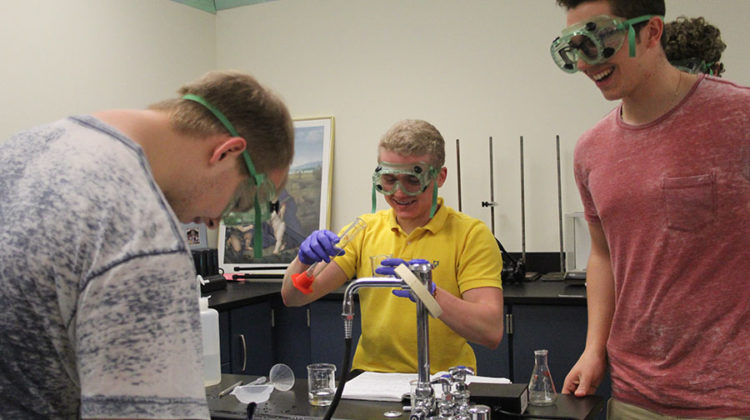 Nathan Jackson (12) pours a measured solution from a graduated cylinder into an empty beaker. One of his lab partners, Kyle Holman (12), took notes in his notebook.