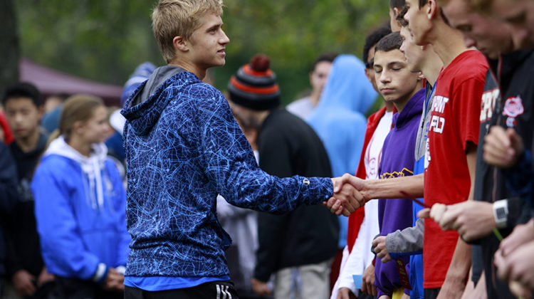 Mitchell Polaski (11) shakes the hand of a runner at the cross country Regionals meet. Polaski has been on the varsity teams of cross country and track since freshman year. Photo by: Ruth Chen (12)