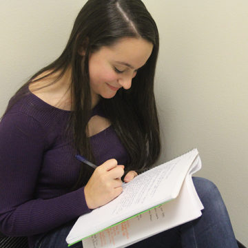 "Emily Gaines (10) writes in her notebook. She has been working on her story ""Are You Afraid of the Dark?"" for over two years."