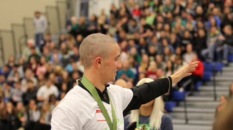 Nicholas Lucas (12) waves to the crowd after getting his head shaved. The assembly took place on March 17.