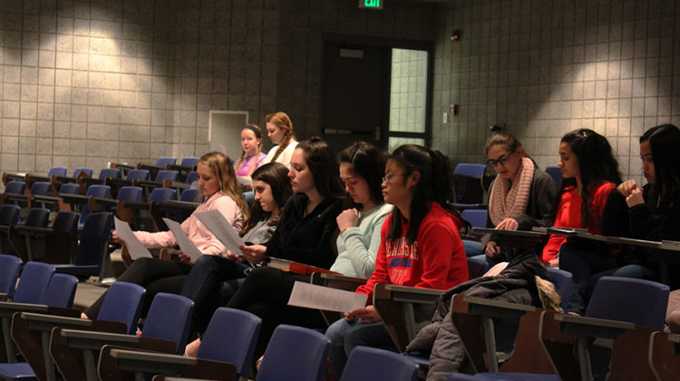 N-Teens students sit and wait for Gabrielle Rapin, Science, and Kelsey Becich, English. They waited for the sponsors to speak about new places and when service hours are due.