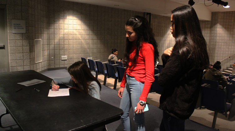 Allison Centanni (9), Veronica Gonzalez (9) and Charmagne Abangan (9) signing their names on the sign in sheet before the meeting starts. Every meeting they have to sign in to show you commitment to the club.