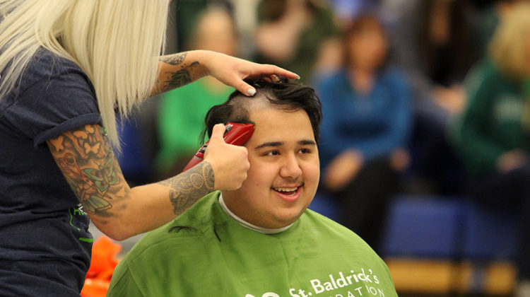 Collin Elliot smiles as gets his head shaved. He was a survivor of the fight through cancer.