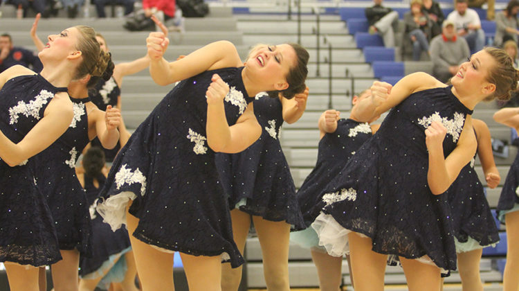 Paige Lambert (9) dances with her teammates during halftime at a basketball game. Lambert danced alongside mostly upperclassmen and is the only freshman on varsity.