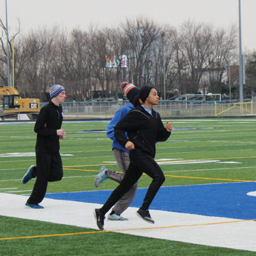 Kelani Benson (11) runs around the football field to warm up. The track team had done a lot of practicing in order to prepare for the upcoming meets.