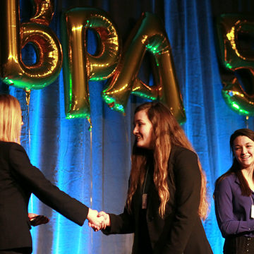 Courtney Carlson (11) smiles as her sister Kayla Carlson (10) shakes a BPA District President's hand after placing tenth in open event Management, Marketing and Human Resource Concepts. Courtney Carlson (11) placed fifth in the same event.