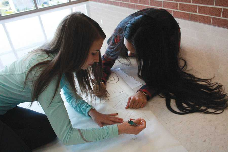 Rachel Eder (11) and Jaskiran Kaur (11) work on posters for the upcoming fundraiser. Interact had set up multiple fundraisers in the past.