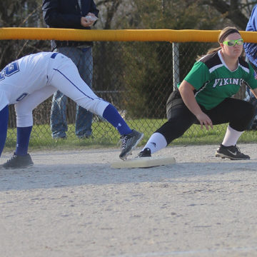 Hanna Hullinger (9) falls as she hits third base. The team has been undefeated since the start of the season.