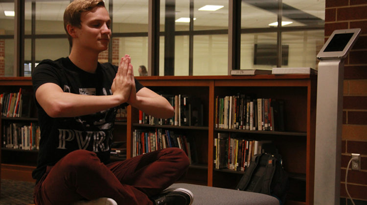 Gavin Baisa (12) sits in the library while doing a yoga pose. Baisa wanted to start the yoga club in order to reduce the stress students feel from school.