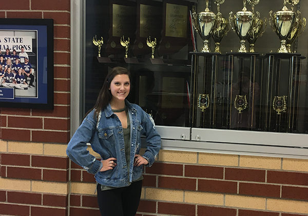 Samantha Schaffer (10) poses outside of the dance trophy case.  Schaffer won one of these while she was still a part of the team.