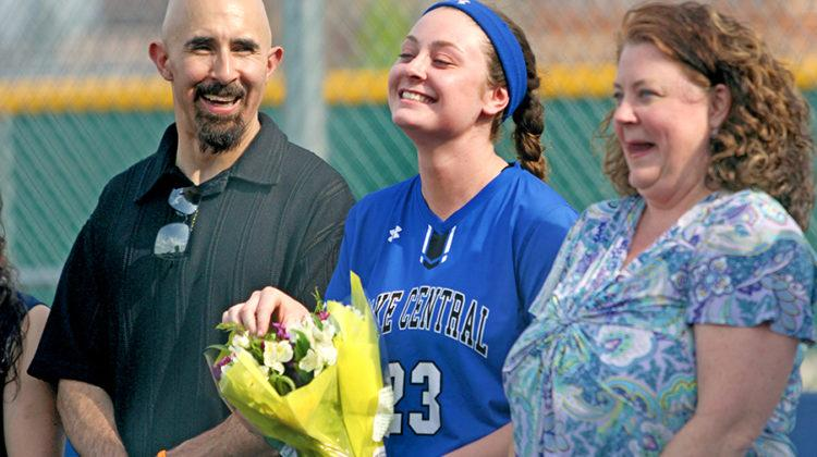 Madison Blythe (12) smiles as with her flowers during the farewell ceremony for senior varsity players. The game was on May 15.