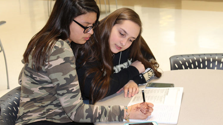 Valeria Escobedo (9) and Nicole Doetterl (9) are take notes for the class cabinet meeting. The club met on May 2, 2017.