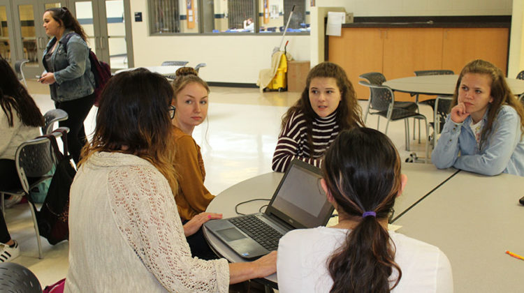Ms. May, Grace Bentkowski (9), Nikki Rytczak (9), and Miranda Prowse (9) discuss when to sell the lanyards. They decided that selling them on Main Street during the lunches was the best option.