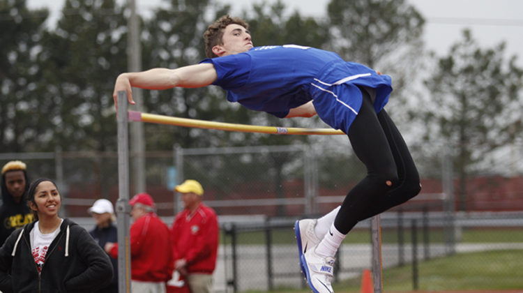 Jack Davis (10) jumps over the high jump bar. Davis had previously qualified for State in this high jump event at an earlier meet.