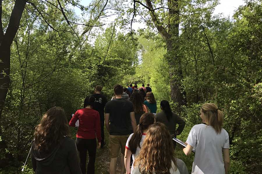 Dr. Dustin Verpooten, Science, leads his second hour class to a pond outside. The lab took place near the cross country course.