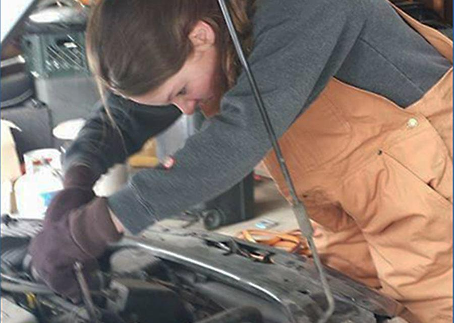 Madilynn Mathison (11) works on a car in her garage. Mathison worked with her dad to try to fix the car.