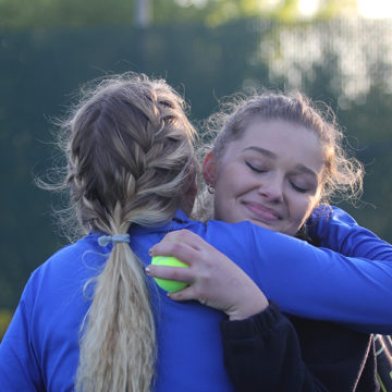 The varsity girls tennis team won at their last home match of the season. Claire Gronek (11) hugged Sky Martens (12) after her and her doubles' partner, Anna Wachowski (12), clinched the win against Valparaiso.