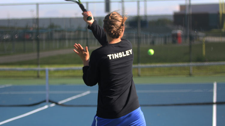 Kristina Tinsley (12) serves the ball during her last home match. Tinsley had never lost a home match during all of her four years.