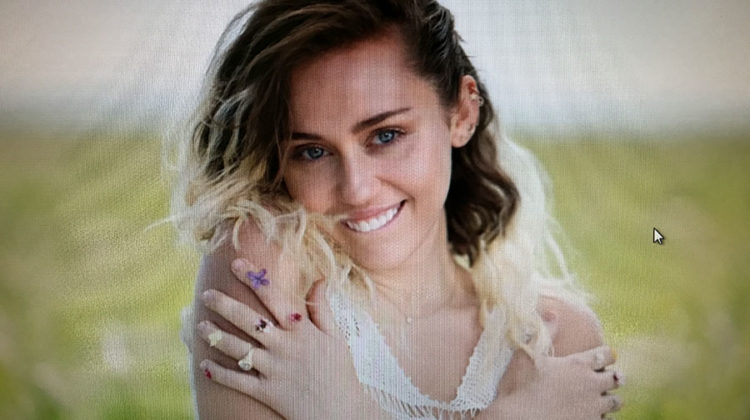 Miley Cyrus sits in the grass along the beach smiling. Cyrus released her single on May 11.