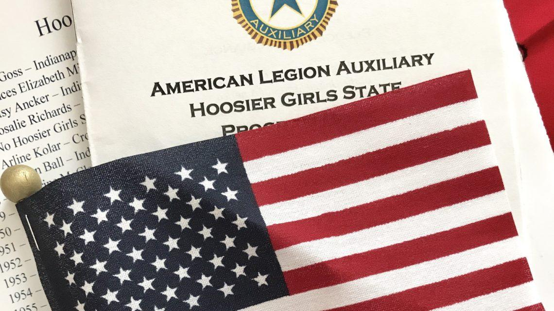 A program from Hoosier Girl's State is displayed with an American flag. The government camp at Trine University emphasized a love for God and country.