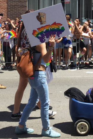 """A person holding up a sign that says, """"PRIDE"""" in rainbow letters and has a multi-colored fist. During the march, there were many people advocating for what they believed in."""