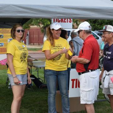 A woman gives a food ticket to a member of the community. There are multiple corn roasts held around the Region over the summer.