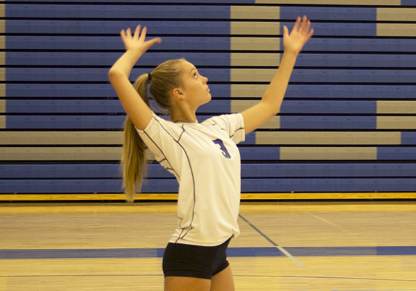 Emma Best (9) serves the ball to the other side on Thursday, September 6th, warming up for the away game at Merrillville High School.