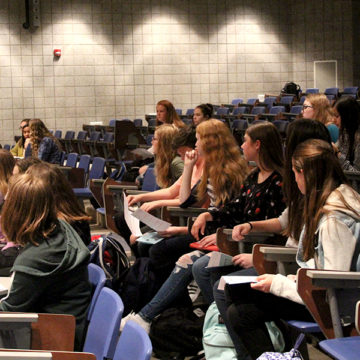 Eliza Hoeckleberg (9) and the other members of her class attentively listen. Mrs. Robin May, counselor, and Mrs. Jamie Rodgers, counselor, explained fundraisers for the class of 2021's school dances.