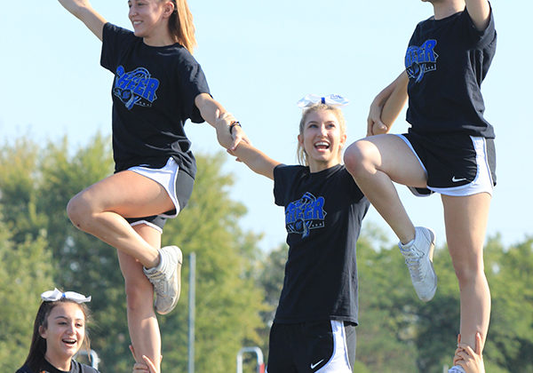 Cheerleaders perform a stunt at the pep rally. The cheerleaders performed during the pep rally.