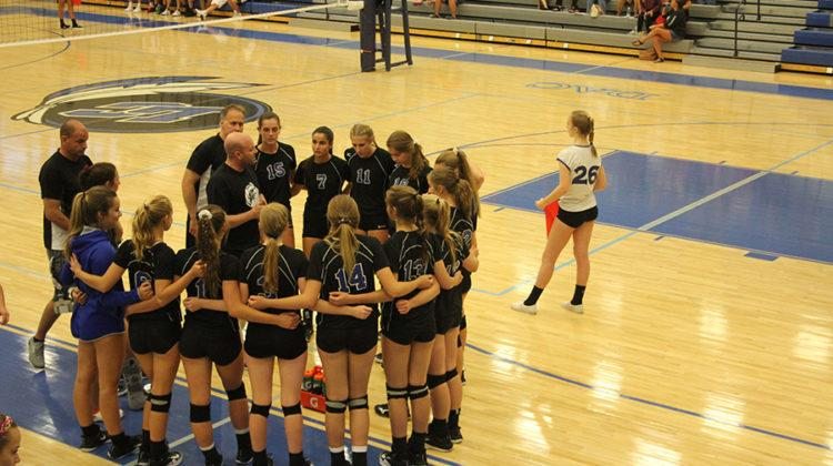 Varsity Volleyball comes together for a team huddle during a timeout. Coach Matt Clark gave them a pep talk during the timeout.