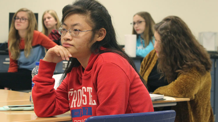 Tina Lin (11) watches Madelyn Ackerman's ('16) presentation. The meeting took place in Mr. Kendal Smith's, Science, room.