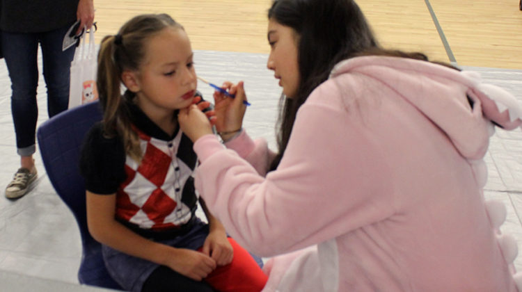 A girl gets her face painted by Ariana Kanaya (11). Some common designs trick-or-treaters had painted throughout the night included a heart, a basketball and a smiley face.