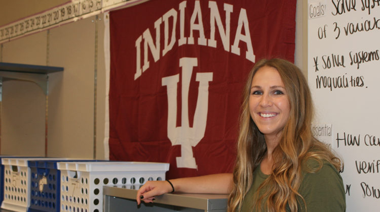 Mrs. Megan Banashak, Mathematics, poses next to her Indiana University banner. Indiana University was the college she graduated from.