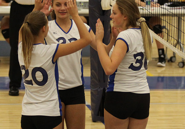Jillian Moore (10),Lilly Robinson (9) and Joie Mulligan (9) high five after they score a point. Although the team struggled during the first half, they managed to pull it together in the second half and pull out a win.She set up many balls for her teammates to spike.