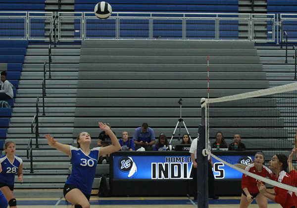 Lily Robinson (9) prepares to spike the volleyball. Robinson followed the ball and prepared to jump.