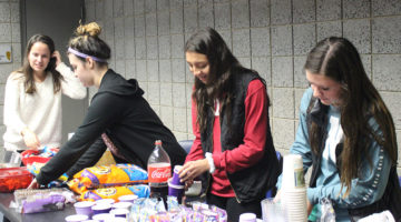 Members of Best Buddies prepare chips, cookies and drinks. The buddies and their peers came up to the table after and got to pick out what food they wanted.