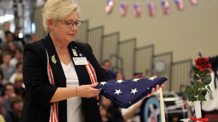 Rose Ann Dzieglowicz assists in the POW/MIA tribute.  Dzieglowicz and her husband presented the table and each object's significance.