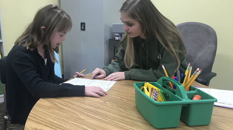 Erin Plenus (12) helps a child she is tutoring with reading. She has helped with tutoring for three years.