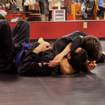 Skrezyna pins down his partner and refuses to let go of his hold.  He spreads his leg to create a stronger hold and buries his head to deny his opponent a chance to reverse the hold.