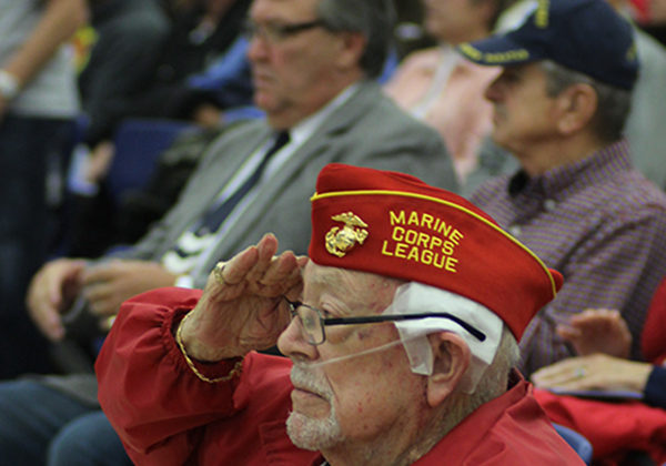 A veteran salutes during the song the United States Armed Forces Medley. The veteran served in the marine corps.