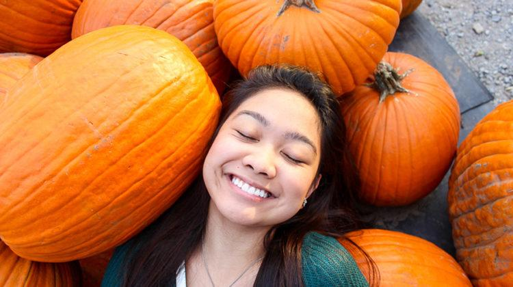 Rheena Molina (12) smiles as she lays around pumpkins. She went to Elzinga Farm Market to look for pumpkins to carve.