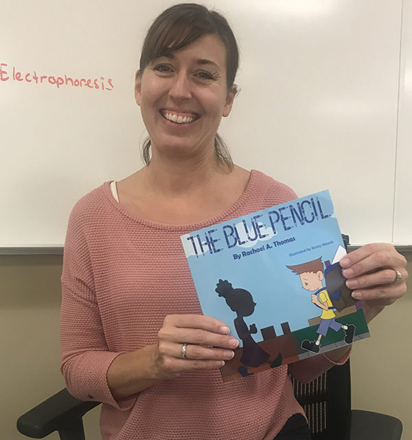 """Mrs. Thomas, Science, holds the book she wrote. It is called """"The Blue Pencil."""""""