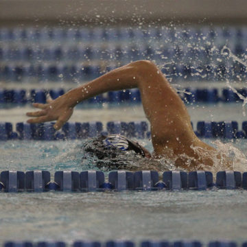 The varsity swimmer races to the end of the race. He used a lot of muscle to swim as fast as he could.